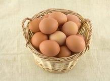 A galinha eggs na cesta de vime no pano bege  Fotografia de Stock