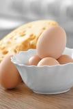 A galinha eggs no prato branco com queijo em um de madeira Fotos de Stock