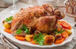 Galinha enchida Natal servida com batatas, cenouras e figos Fotografia de Stock