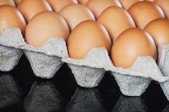 A galinha fresca eggs no pacote cinzento do cartão da bandeja de papel na tabela preta do espelho Fotografia de Stock