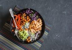 Galinha grelhada, arroz, grãos-de-bico picantes, erva-benta do abacate, couve, bacia de buddha da pimenta no fundo escuro, vista  Fotos de Stock Royalty Free