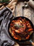 Galinha grelhada com batatas e vegetais em uma frigideira do ferro fundido em um fundo rústico de madeira Close-up Vista foto de stock royalty free