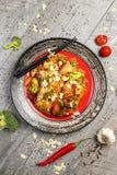 Galinha grelhada em uma placa preta, situada ao lado dos vegetais, das pimentas vermelhas e dos hashis Fotografia de Stock Royalty Free