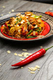 Galinha grelhada em uma placa preta, situada ao lado dos vegetais, das pimentas vermelhas e dos hashis foto de stock