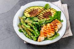 Galinha grelhada saudável, abacate grelhado e salada do aspargo com sementes de linho Almoço equilibrado na bacia Ardósia cinzent Foto de Stock Royalty Free