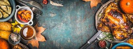 A galinha inteira ou o peru roasted delicioso na placa com cutelaria e molho, colheita grelharam vegetais no fundo rústico escuro Imagem de Stock Royalty Free