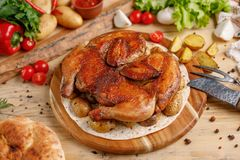 A galinha suculenta do cigarro com batata decora em uma placa de madeira redonda Imagens de Stock Royalty Free
