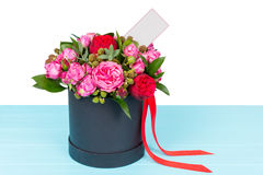 Gallant bouquet of pink and red roses with a blank gift tag with. Copy space and red ribbon in a circular black box. Valentines and anniversary concept Stock Image