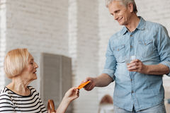 Gallant caring man making sure his lady getting better. Time to get better. Admirable handsome aged gentleman giving his wife the pills she needing for Royalty Free Stock Photo