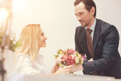 Gallant charming man greeting his colleague. Pleasant gesture. Handsome attentive friendly gentleman presenting a bouquet and wishing a leady all the best while Royalty Free Stock Images