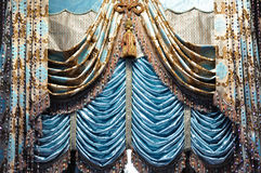 Gallant curtain with decoration. Detail of curtain with edging and tassel in blue shining color, which is gorgeous, heavy and complicated design Stock Photo