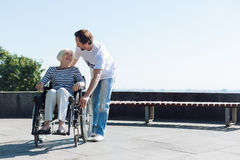 Gallant enthusiastic volunteer asking if everything is ok. Take good care of yourself. Handsome kind attentive men making sure elderly lady doing fine while they Royalty Free Stock Images