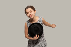 Gallant girl with hat. Gallant girl taking off her hat, portrait in studio Royalty Free Stock Photo