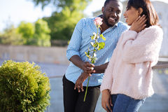 Gallant handsome guy surprising his girlfriend. Beauty for beauty. Young polite charming men asking a girl out on a date and showing up holding nice flower in Stock Images