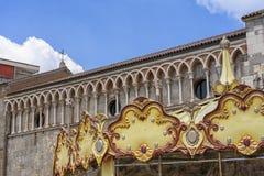 Gallarate, Italy: San Pietro church. Gallarate, Varese, Lombardy, Italy: exterior of the medieval San Pietro church and a carousel Stock Photos