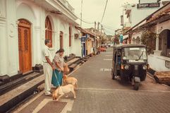 Elderly couple with dogs walking past tuk-tuk driving in historical city. GALLE, SRI LANKA - DEC 23, 2017: Elderly couple with dogs walking past tuk-tuk driving Stock Photography