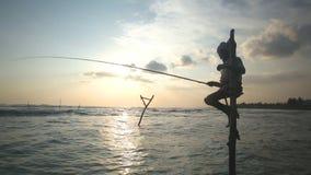 GALLE, SRI LANKA - EM MARÇO DE 2014: Silhueta do pescador idoso em um polo de pesca no por do sol A pesca do pernas de pau é uma  filme