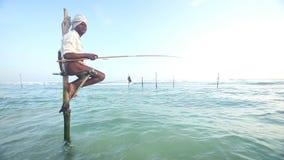 GALLE, SRI LANKA - MÄRZ 2014: Alter Fischer auf einer Angelrute im Ozean in Galle Stelzenfischen ist eine Tradition, die nur über stock video footage