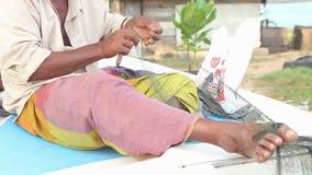 GALLE, SRI LANKA - MÄRZ 2014: Lokaler Fischer, der auf Boot und Reparierenfischernetzen sitzt Diese Leute finden es schwieriger z stock footage
