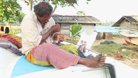 GALLE, SRI LANKA - MÄRZ 2014: Lokaler Fischer, der auf Boot und Reparierenfischernetzen sitzt Diese Leute finden es schwieriger z stock video