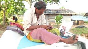 GALLE, SRI LANKA - MÄRZ 2014: Lokaler Fischer, der auf Boot und Reparierenfischernetzen sitzt Diese Leute finden es schwieriger z stock video footage