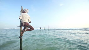 GALLE, SRI LANKA - MARCH 2014: Old fisherman on a fishing pole in the ocean in Galle. Stilt fishing is a tradition that only about