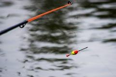 Galleggi sull'acqua con una linea di pesca Fotografia Stock