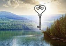 galleggiamento chiave del cuore 3D sopra il lago della montagna Immagine Stock