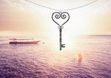 galleggiamento chiave del cuore 3D sopra il tramonto del mare Fotografie Stock