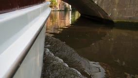 Galleggiando in una barca sul canale nella città e sulla nuotata sotto il ponte video d archivio