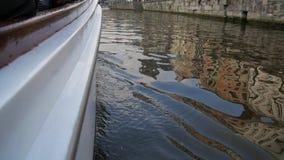 Galleggiando in una barca sul canale nella città lungo le pareti di pietra stock footage