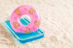 Galleggiante gonfiabile nella piccola piscina sull'estratto della spiaggia immagine stock