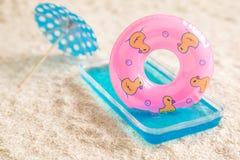 Galleggiante gonfiabile in piccolo parasole della carta e della piscina sull'estratto della spiaggia fotografie stock