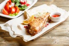 Galler för havsbas Tjäna som på ett träbräde på en lantlig tabell Meny för grillfestrestaurang, en serie av foto av olikt Fotografering för Bildbyråer