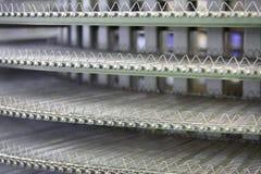 Galler och transportör för att steka köttbullar och andra köttprodukter. Arkivbild