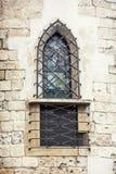 Gallerförsett fönster på den kyrkliga väggen Royaltyfri Foto
