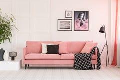 Galleri av affischer på väggen i trendig vardagsrum som är inre med den rosa soffan och den industriella lampan royaltyfri fotografi