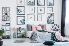 Gallerit med enkla affischer som hänger på väggen i ljus sovruminre med många, kudde på säng, nya växter och plast- chai royaltyfri fotografi