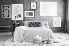 Gallery in bedroom interior. Simple gallery on grey raw wall in bedroom interior with boxes placed by the bed stock photography