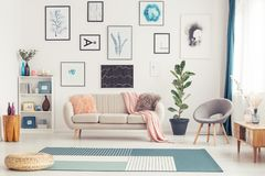 Gallery in bright living room. Pouf on blue carpet in bright living room interior with grey chair and settee against the wall with gallery Royalty Free Stock Images