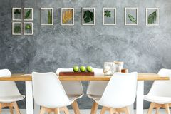 Gallery of framed tropical leaves. Hanging on gray textured wall in minimalist dining room with wooden table and white chairs stock photo