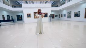 Gallery hall with a gorgeous woman playing the violin stock video