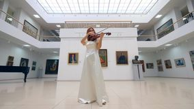 Gallery hall with a lady skillfully playing the violin. 4K stock video