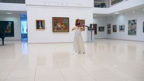 Gallery hall with a lady violinist playing the instrument. 4K stock video