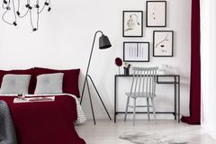 Gallery of illustrations on a white wall above a small desk which is next to a black metal lamp and a burgundy bed in a modern b. A gallery of illustrations on a stock image