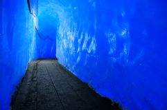 Gallery inside a glacier. A tunnel cut inside the rhone glacier, with planks on the floor, and cables along the ceiling for lighting. Blue light filters through Royalty Free Stock Image