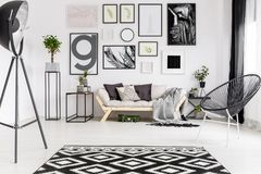 Gallery in modern living room. Gallery of posters above settee in modern living room interior with patterned carpet next to lamp Stock Photos