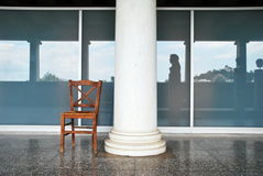 Glas, reflections, big column and lonely chair royalty free stock images