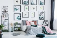 Gallery with simple posters hanging on the wall in bright bedroom interior with many pillows on bed, fresh plants and plastic chai. R standing next to window royalty free stock photography