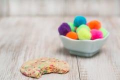 Galleta colorida del confeti mordida con las bolas decorativas foto de archivo libre de regalías